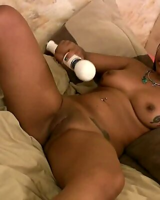 Busty tanned girl using a toy to cum